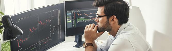 Man looking at computer screens at a desk